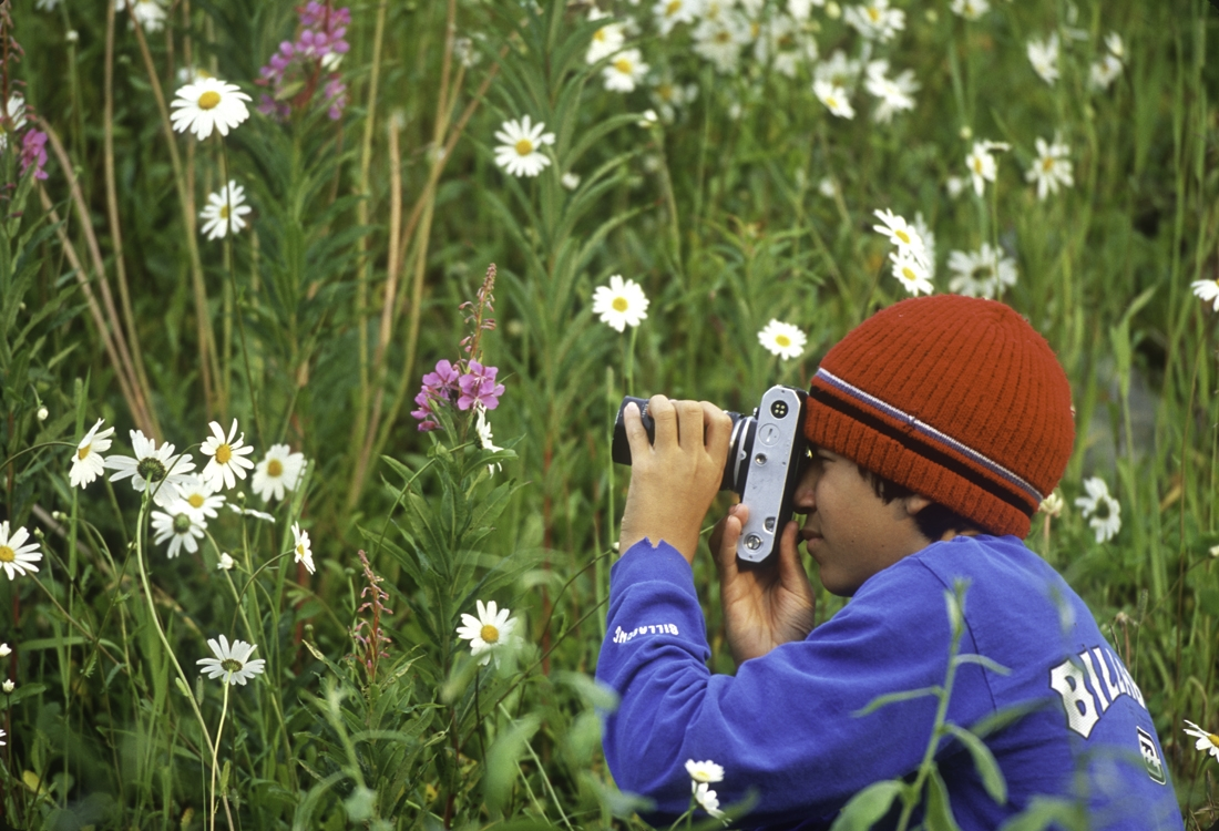 Young man photographing flowers