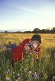Child looking at flowers with magnifying glass